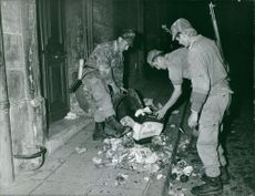Soldiers checking garbage from the dustbin. 1961