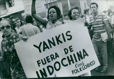 """Demonstrators hold a placard reading """"Yankees Get Out of Indochina,"""" during a protest in the streets of Cuba."""