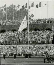 The Olympic flag is elevated to the tones of the Olympic Hymn