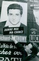 Georges Poubennec looking at his own posters in street and smiling.