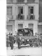 Military and trucks on the street with barricades, in Algeria, 1960.