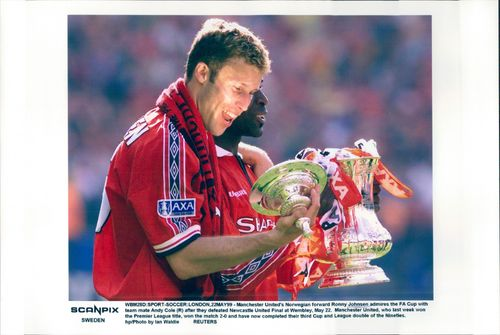 Manchester United's players Ronnie Johnsen and Andy Cole admire the cup they won in the FA Cup