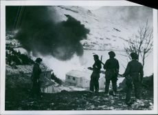 Group of soldiers standing and looking at the burning house. 1942