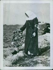 The War: Russian Red Cross nurse at a graveside planted with a cross made out of shrapnel cases; it is the burial place of an officer.
