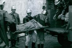 Firemen carrying a student in a stretcher, a casualty from fire, in Vietnam, 1968.