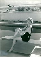 Actress Grace Moore sits on a trampoline to a pool