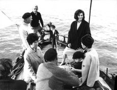 Rita Hayworth standing on boat with people.