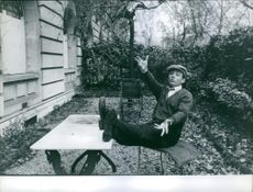 1959 A photo of a French actor Claude Brasseur sitting on chair while he is raising his hands.