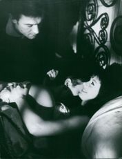 A woman lying on bed with a man closely.