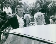 Susan Zanuck with her husband, André Hakim going inside the car,