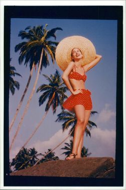 A woman wearing red two piece and big hat.