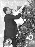 Prince Juan of Spain holding his child decorating the Christmas tree.