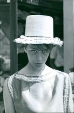 Portrait of a woman wearing a big hat looking something.