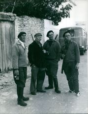 1962  A photo of men standing together, holding gun and smoking in the road.