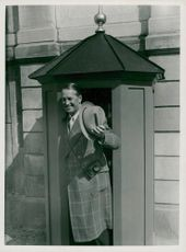 Maurice Chevalier poses at guard cages
