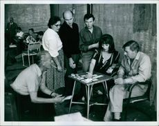 Men and woman playing card together.