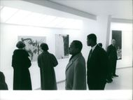 Felix Houphouet-Boigny looking at paintings.