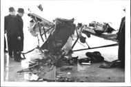 Aviation accident where men stand and look at the wreckage of the aircraft.