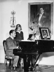 "Johan Jonatan ""Jussi"" Björling playing piano with his daughter standing beside him."