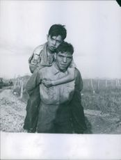 Boy carrying his wounded friend on shoulder and walking in the field in Indo China