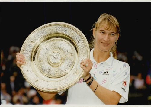 Steffi Graf proudly holds up his Wimbledon trophy