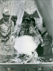 Woman standing and traditional activity during marriage.
