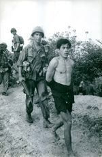 A soldier walking behind a captured man. Vietnam.