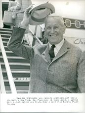 Maurice Chevalier standing and smiling.