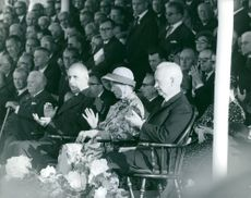 Leaders of Luxembourg applauding, with people at their back, watching, 1964.