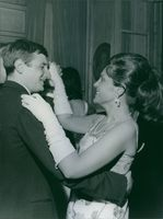 Man and woman dancing together during a party and smiling.