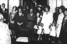 Frederica of Hanover, Infante Juan, Juan Carlos and Sofia of Spain standing with group of people.