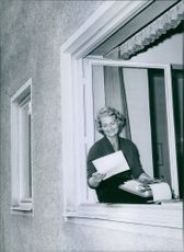 Princess Elisabeth reading a letter and smiling sitting on a window. 1935