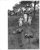 A motorcycle rider crashed on a hill and being helped by men.