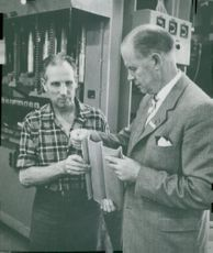Answers. Production Manager Carl Sågvall, together with the press presser Georg Olsson, looks at a detail from office furniture production