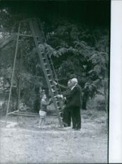 Men standing in the park, beside the swing and talking to child.