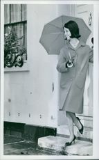 Year ? A photo of a woman posing and holding umbrella looking something in front of a door.
