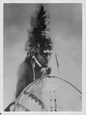 A man dressed in a native costume holding a spear and shield.