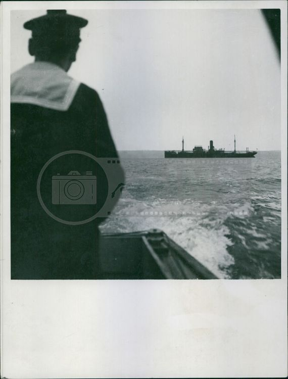 A photo of a Navy man facing the sea looking at a cargo vessel.