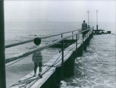 A little girl following a man to the dock.