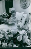 A patient siting on bed, holding bundle of envelope.