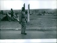 A soldier is standing on the road and laughing during 1958 Lebanon crisis, a temporary camp behind of him