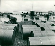 Oil drums being unloaded from a Lockheed C-130 Hercules plane during Zambia Crisis 1965