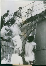 Japanese prisoners crawl up the landing net to board a U.S. transport off shore.