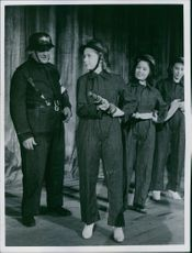 A man standing beside the Scala Girls holding a fire hose in 1940.