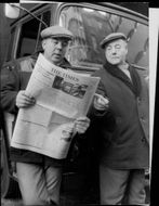 Two men are reading a newspaper