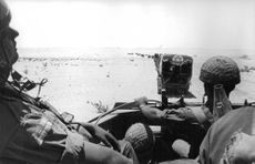 Soldiers driving on a desert.