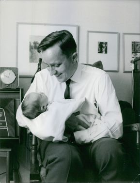 A smiling father cuddling with his newborn baby.