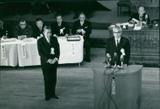 Man delivering speech on a podium.