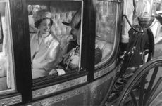 Princess Anne sitting in a royal cart and talking to a man.