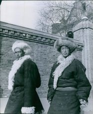 Men standing and looking at camera, wearing warm coat.